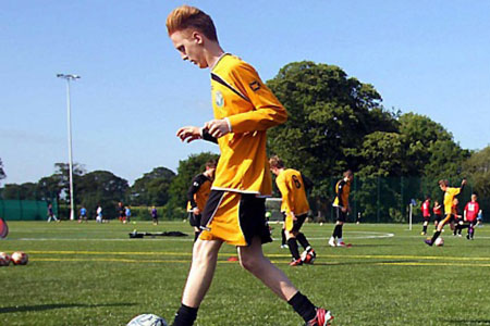 Christleton High School student playing football in PE Kit
